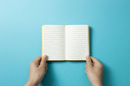 Hands open empty notebook on blue background. top view, copy space