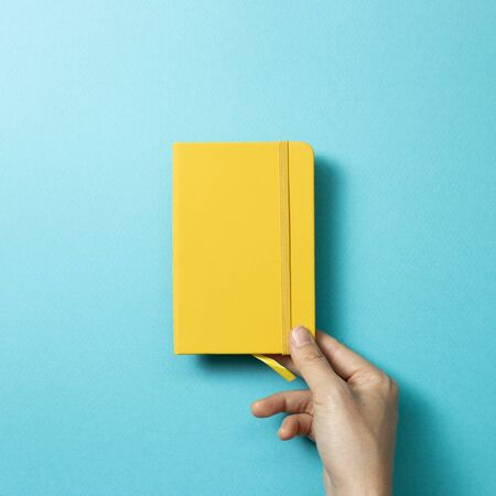 Hand holding yellow diary notebook on blue background. top view, copy space Zdjęcie Seryjne