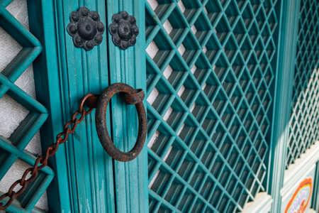 Korean traditional green wooden door and rusty doorknob 免版税图像