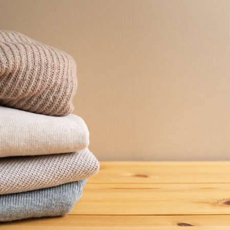Pile of warm sweater clothes on wooden table. Autumn and winter concept. with copy space 免版税图像 - 152694546