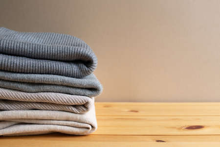 Pile of warm sweater clothes on wooden table. Autumn and winter concept. with copy space
