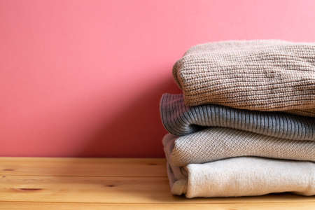 Pile of warm sweater clothes on wooden table. Autumn and winter concept. with copy space 免版税图像 - 152694552