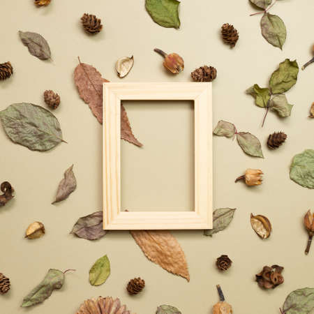 Wooden photo frame with autumn dry leaves on khaki brown background. flat lay, top view, copy space