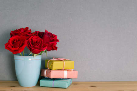 Red rose flowers with gift boxes on wooden table with gray background. floral arrangement, copy space