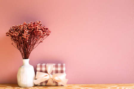 Gift box with red sinensis dry flower on wooden table with pink background 免版税图像