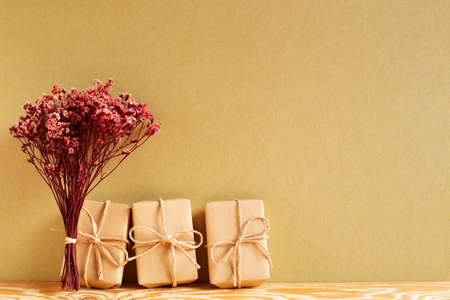 Gift boxes with red sinensis dry flower bouquet on wooden table with khaki brown background