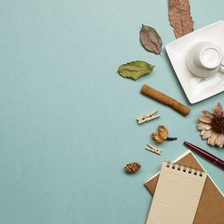 Autumn concept. Notebook and mug cup with dry leaves on green background. flat lay, top view, copy space. Work and study place 免版税图像