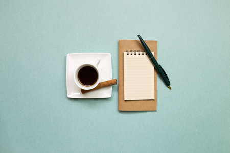 Notebook and black coffee on green background. flat lay, top view, copy space. Work and study place