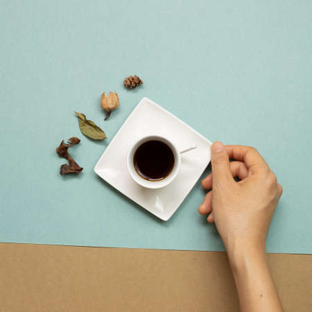 Hand holding cup of coffee with autumn dry leaves on green and brown background. flat lay, top view 免版税图像