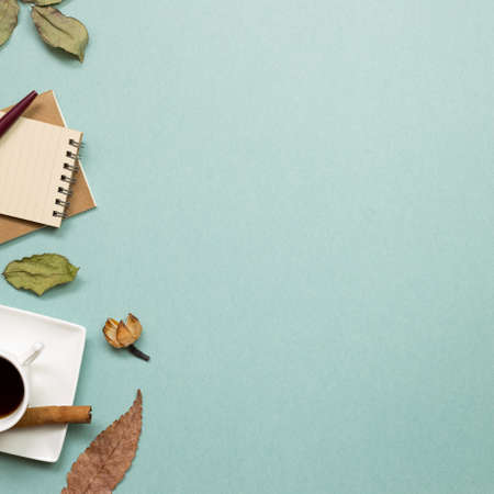 Autumn concept. Notebook and black coffee with dry leaves on green background. flat lay, top view, copy space. Work and study place