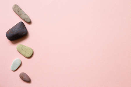 Natural pebble stones on pink background. top view, copy space