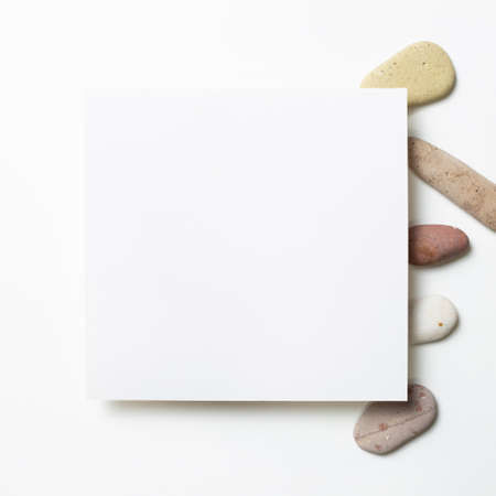 White memo pad, empty paper with pebble stones on white background. flat lay, top view, copy space