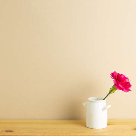 Vase of pink carnation flower on wooden table with beige background