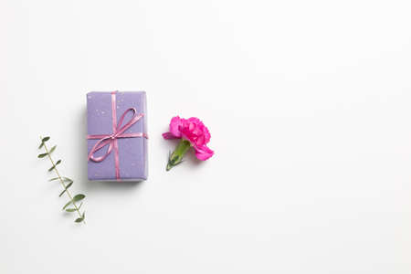 Purple gift box with carnation flower on white background. flat lay, top view, copy space
