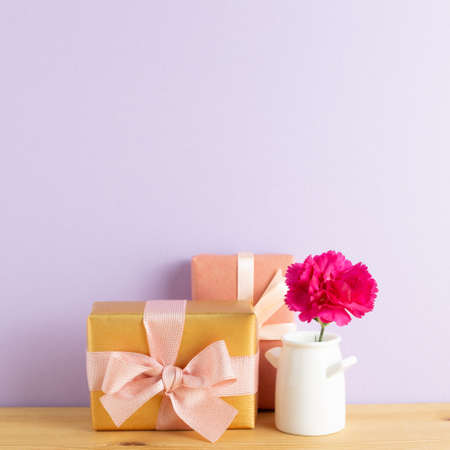 Gift boxes with vase of pink carnation flower on wooden table with purple background