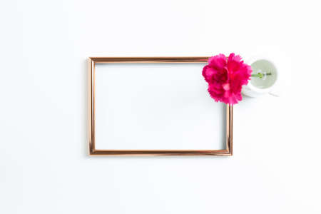 Photo frame with pink carnation flower on white background. flat lay, top view, copy space 免版税图像