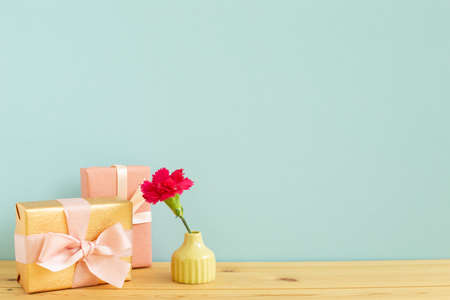Gift boxes with vase of pink carnation flower on wooden table with blue background 免版税图像