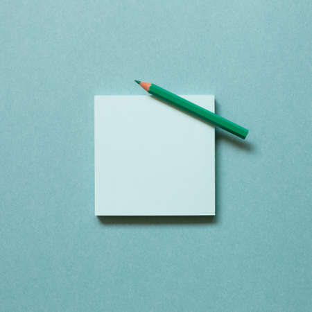 Green memo paper, sticky notes with colored pencil on green background. top view, copy space