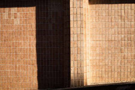 Brown tile wall and sun light shadow