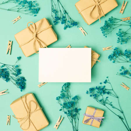 Empty memo paper with gift boxes and gypsophila dry flowers on green background. flat lay, top view, copy space