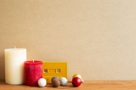 Winter concept. Candles, audio cassette tape, decor balls on wooden table. Brown background