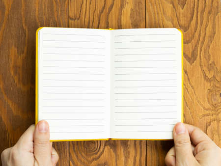 Hands open empty notebook on wooden desk. top view, copy space