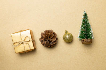 Christmas concept. Gift box with fir tree, bauble, pine cone on brown background. top view