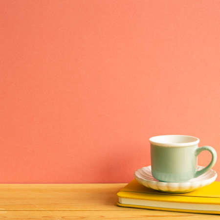 Coffee cup with notebook on wooden table. Pink background