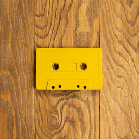 Yellow audio cassette tape on wooden table. top view, copy space