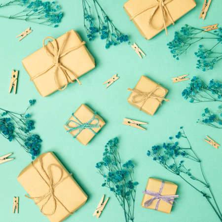 Gift boxes with gypsophila dry flowers on green background. flat lay, top view Stock Photo