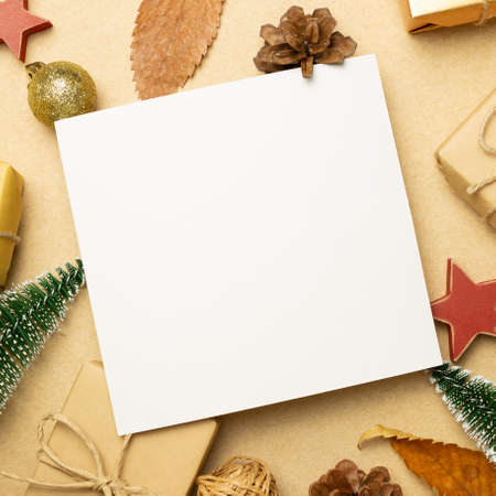 Empty memo paper with gift boxes and Christmas ornament on brown background. flat lay, top view, copy space