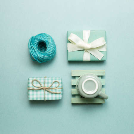 Gift boxes, coffee cup, string roll on mint green background. flat lay, top view, copy space