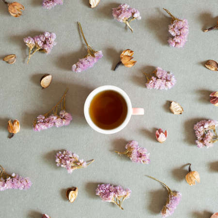 Cup of black tea with dry flowers on gray background. top view