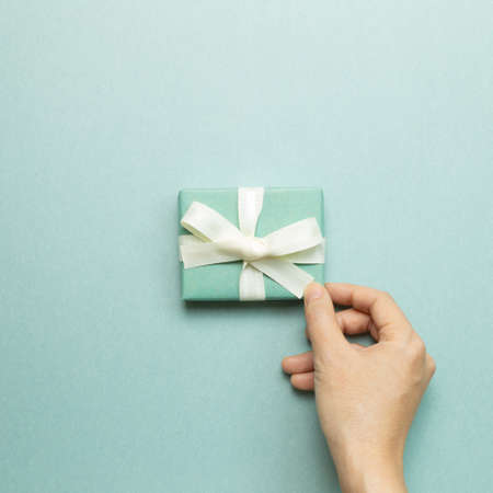 Hand holding mint green gift box on mint green background. top view, copy space