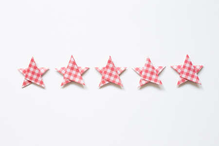 Red check pattern five stars quality rating on white background. top view Stock Photo