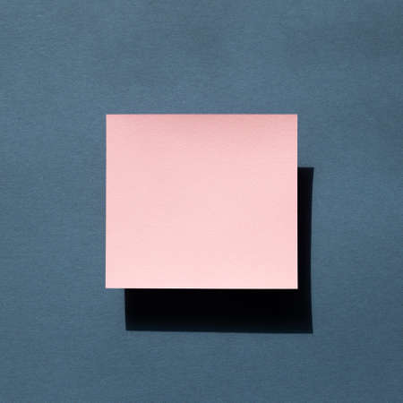 Pink Memo pad on navy blue background. top view, copy space 免版税图像
