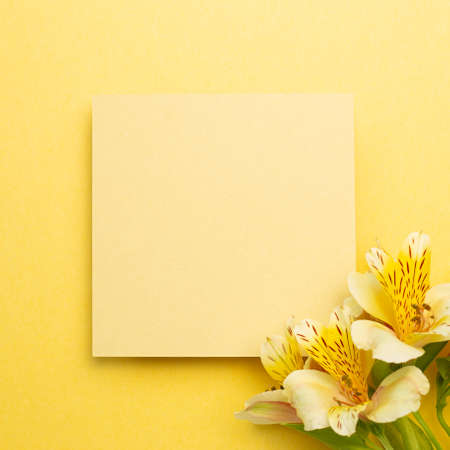 Memo pad with Alstroemeria flowers on yellow background. top view, copy space