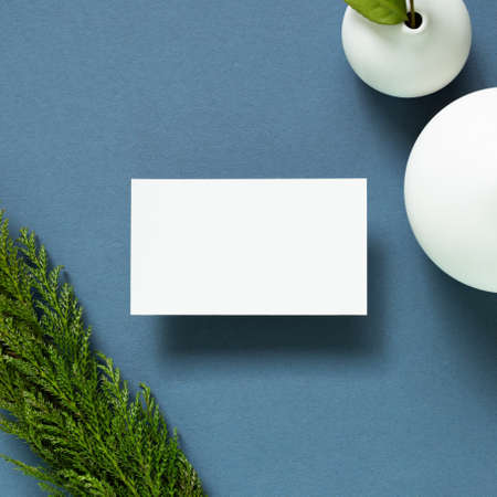 Blank white business card with vase of plant on desk. navy blue background. flat lay, top view, copy space