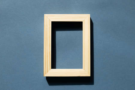 Wooden picture frame on navy blue background. top view, copy space