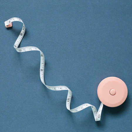 Pink tape measure on navy blue background. top view, copy space 免版税图像
