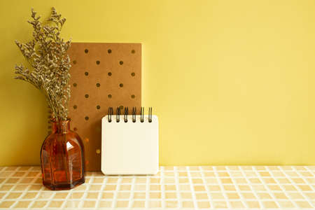 Notebooks and vase of misty blue dry flowers on beige ceramic mosaic tile desk. yellow wall background. Work and study place