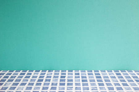 Blue ceramic mosaic tile table. mint wall background. home interior