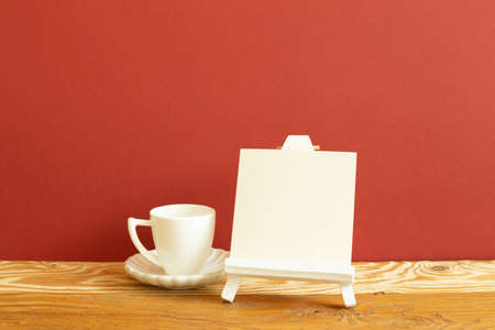 Easel with blank canvas and white coffee cup on wooden table. red background 免版税图像