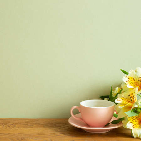Coffee cup with yellow alstroemeria flowers on wooden table. khaki green background