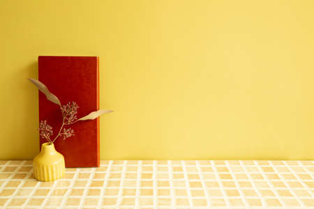 Notebook and vase of dry flowers on beige ceramic mosaic tile desk. yellow wall background. Work and study place