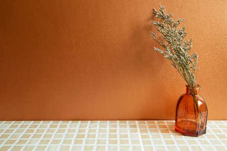 Vase of misty blue dry flowers on beige ceramic mosaic tile table. Orange background. home interior 免版税图像