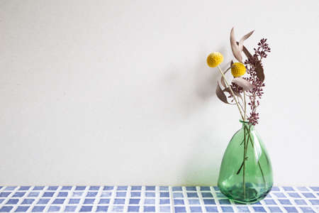 Vase of dry flowers on blue ceramic mosaic tile table. white wall background. home interior