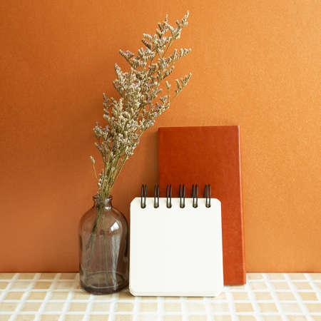 Notebooks and vase of misty blue dry flowers on beige ceramic mosaic tile desk. Orange background. Work and study place