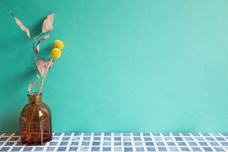Vase of dry flowers on blue ceramic mosaic tile table. mint wall background. home interior 免版税图像