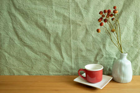 Red coffee cup and vase of orange dry flowers on wooden table. green fabric background. home interior
